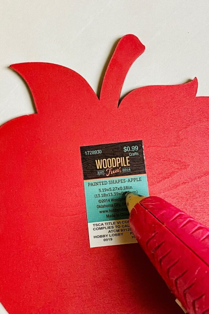 putting hot glue on apple wooden cutout