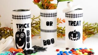 halloween tins on a white table with candy and Halloween toys around it